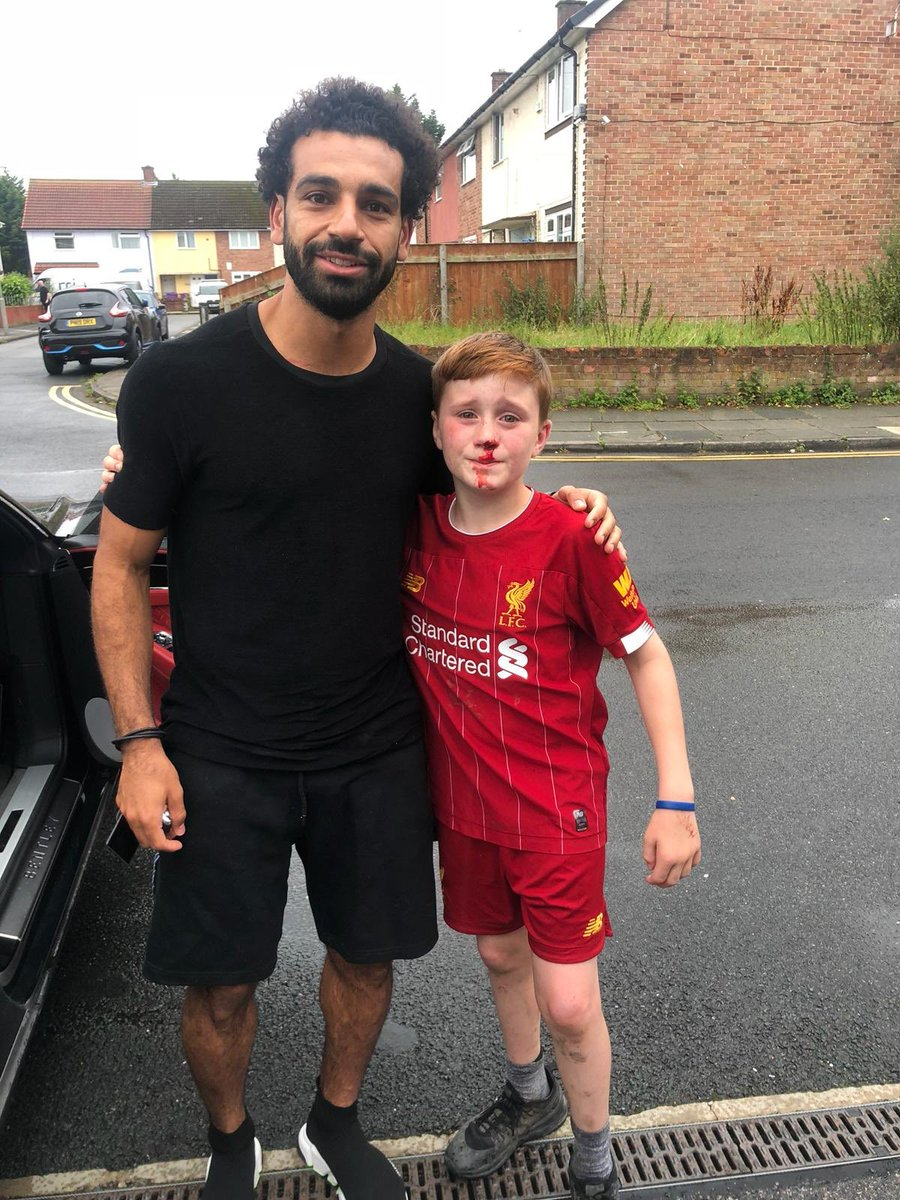 Mohamed Salah poses with young fan who ran into lamp post trying to get a wave