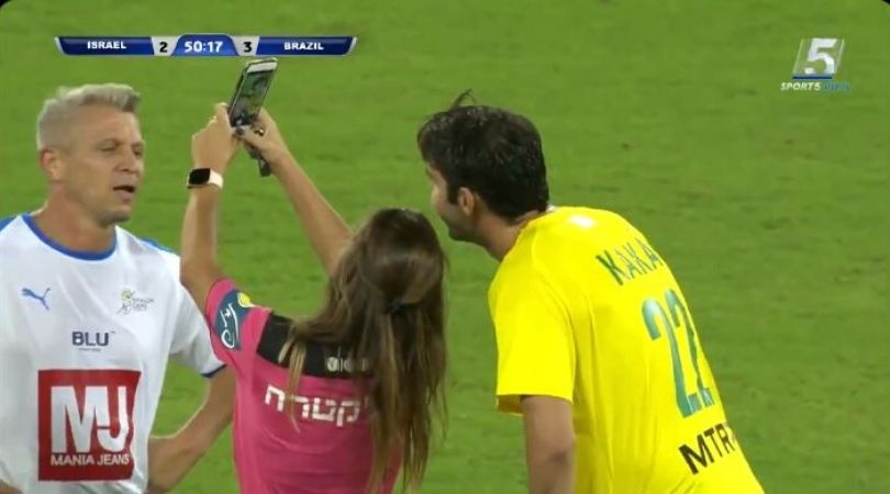 Referee shows Kaka yellow card before taking a selfie with him during a game